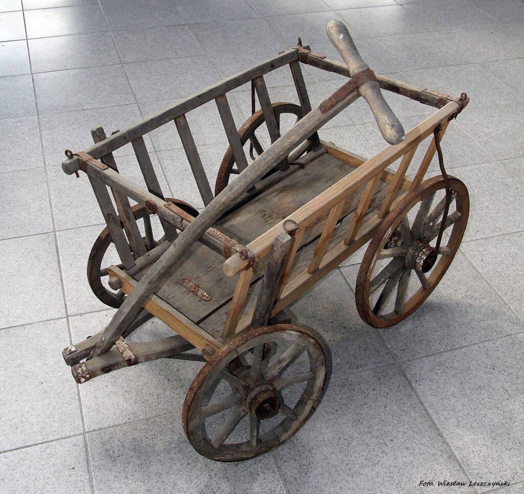 Wózek ze złożonym dyszlem, poza zachowanym oryginalnie drewnem widoczne zardzewiałe metalowe okucia mocujące oraz obramowanie drewnianych kół. Zdjęcie wykonane z góry, skierowane zostało na prawą stronę wózka ze szczebelkami wykonanymi z nowego drewna.