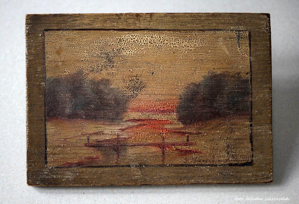 Zdjęcie przedstawia obraz namalowany na desce, całość utrzymana w ciepłej tonacji kolorystycznej, dominuje brąz i czerwień. Na pierwszym planie namalowany most i kręta rzeka, tło bardziej rozmyte.