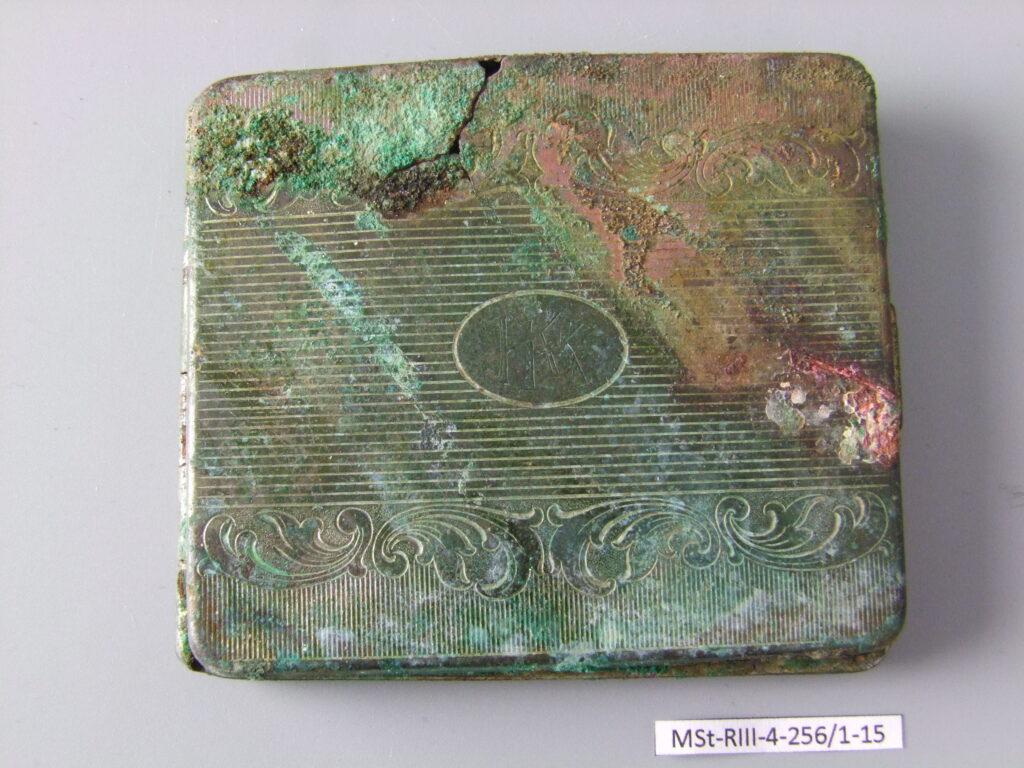 Zdjęcie wieczka zabrodzonej, skorodowanej w niebieskim kolorze papierośnicy. Na wieczku grawerowana elementami ozdobnymi oraz inicjałami KK.