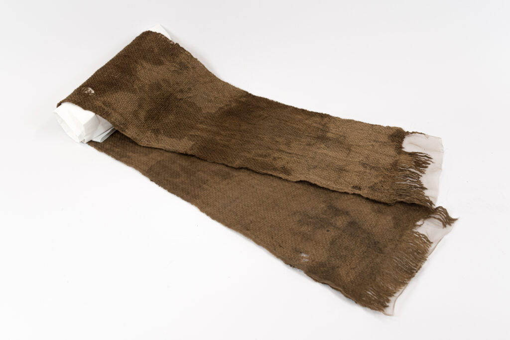 Szalik w kolorze brązowym i żółtym, z podklejonym brązowym jedwabiem w miejscu zniszczeń, rozprostowany i wyczyszczony.