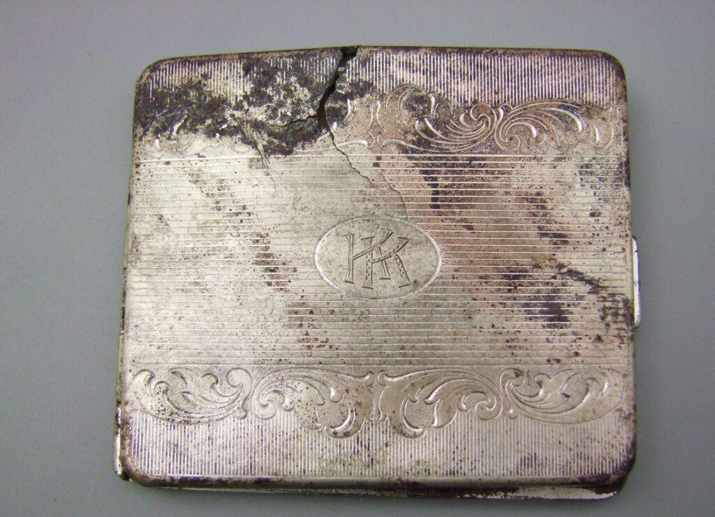Zdjęcie wieczka wyszczyszczonej papierośnicy. Na wieczku grawerowana elementami ozdobnymi oraz inicjałami KK.