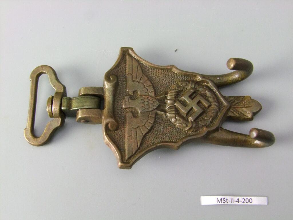 Zdjęcie wyczyszczonego zaczepu do werbla formacji SA, zbliżenie skierowane na nazistowskiego orła z rozłożonymi skrzydłami trzymający w szponach wieniec laurowy ze swastyką w środku. Na dole wyprofilowane dwa haki (jeden umieszczony nieco wyżej od drugiego). Na górze umieszczono obrotowe zaczepienie do paska.