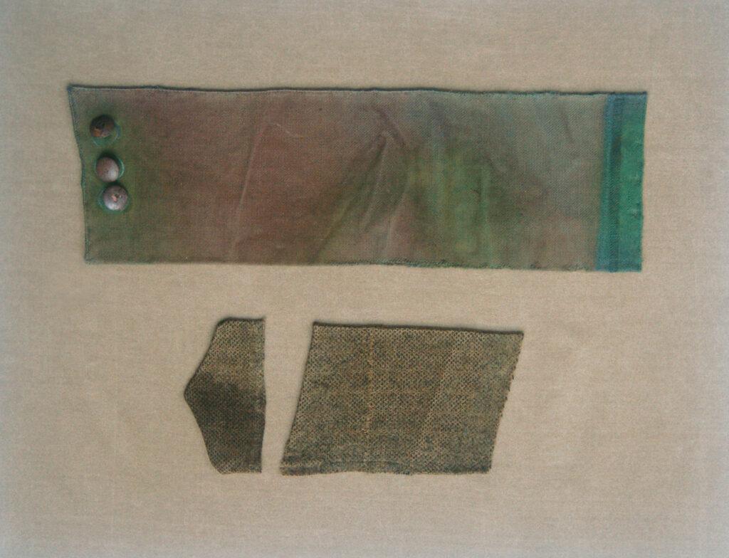 Fragment marynarki w kolorze khaki z doszytymi z lewej strony trzema metalowymi guzikami. Poniżej dwa fragmenty płóciennych patek w kolorze khaki. Wszystkie tkaniny wyszczyszczone, rozprostowane i ułożone na płasko na podstawie wykonanej z tkaniny barwionej w kolorze jasnego brązu.