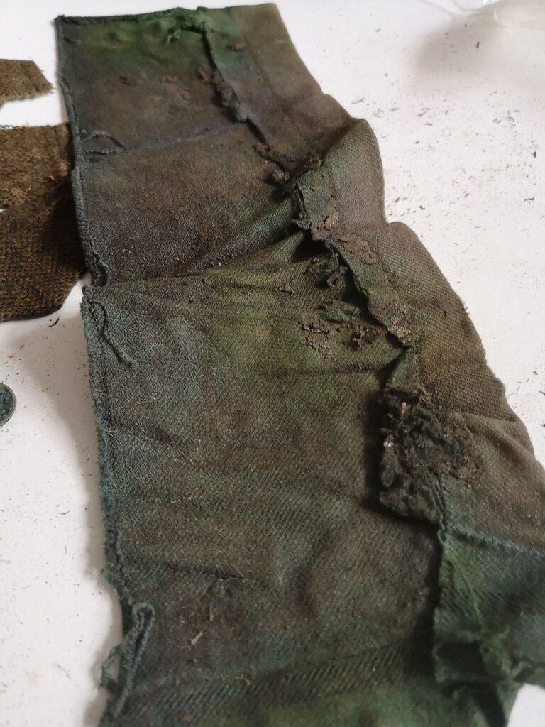 Fragmenty marynarki w kolorze khaki, zabrudzonej i pozginanej.
