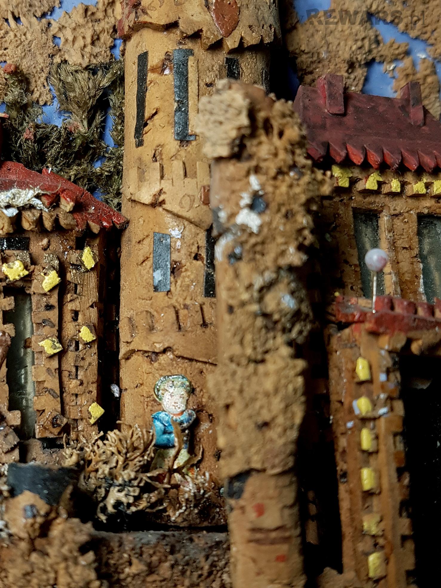 Widoczny fragment jedej wieży, wykonanej z kartonu w kolorze zółtym. Przed wieżą, schowany za krzaczkiem zrobionym z suszonego mchu, widoczny chłopiec w niebieskiej bluzce.