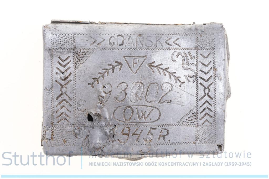 Wieczko grawerowanej papierośnicy. Zbliżenie na wprost. Od góry grawerowana napisami Gdańsk, trójkątem z literą P pośrodku, numerem obozowym 93002, datą 1945 r.