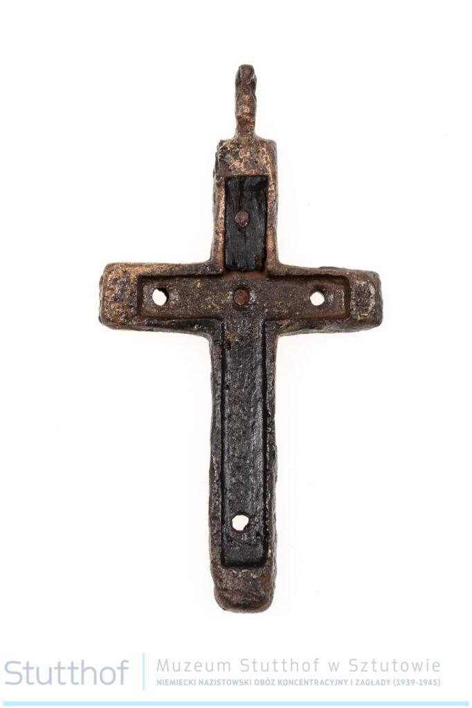 Krzyżyk z mosiądzu. Zdjęcie na wprost. Wewnątrz krzyżyka otwór, w którym pierwotnie znajdowało sie wypełnienie w kształcie krzyżyka. W trzech ramionach otwory po gwoździkach do mocowania.