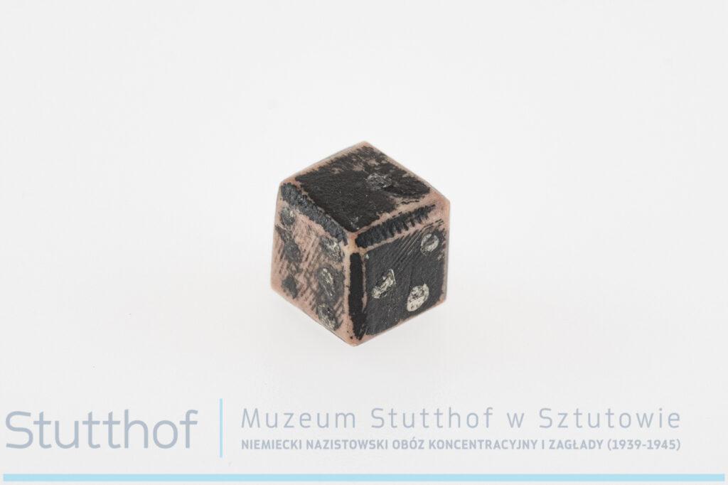 Kamienna kostka pomalowana kolorem czarnym, imitowana na kostkę do gry,