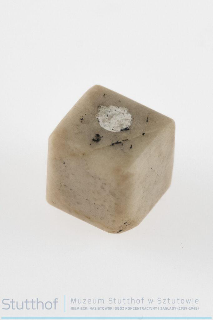Kamienna kostka wykonana z jasnego granitu, miejsce umieszczenia wewnątrz prochów zaślepione białą masą.
