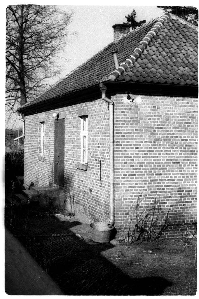 Budynek psiarni obozowej. Zdjęcie czarno białe, widok od strony południowej na drzwi zewnętrzne.