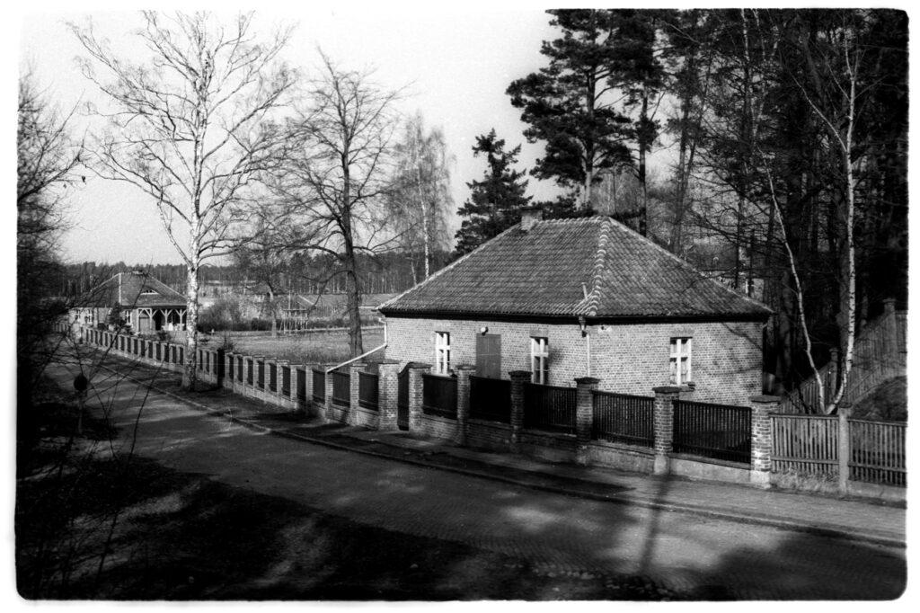 Budynek psiarni obozowej. Zdjęcie czarno białe, widok od strony południowej, w tle widoczna wartownia oraz ogrodzenie Starego Lagru