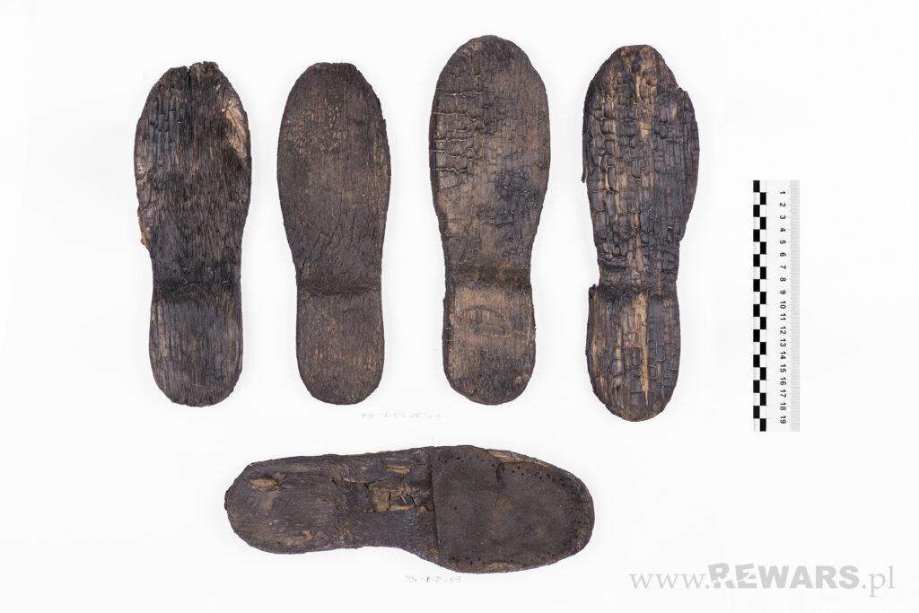 Pięć drewnianych podeszw obuwia, ułożone osobno, widoczny płyn konserwujący w kolorze ciemnym