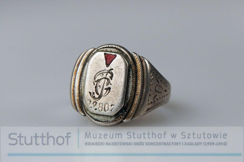 Srebrny sygnet, grawerowany, rzut na oczko oraz fragment grawerowanej obrączki. Zdjęcie wykonane na szarym tle, poniżej znak wodny-logo Muzeum Stutthof.