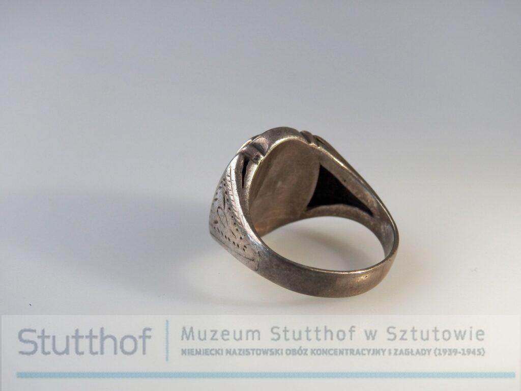 Srebrny sygnet, grawerowany, rzut na oczko oraz fragment Srebrny sygnet, rzut skierowany na obrączkę oraz część tylną oczka. Zdjęcie wykonane na szarym tle, poniżej znak wodny-logo Muzeum Stutthof.