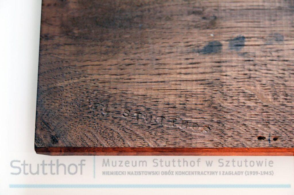 """Tylna część płaskorzeźby, obiekt skierowany na wytłoczony drukowanymi literami napis """"KL Stutthof"""""""